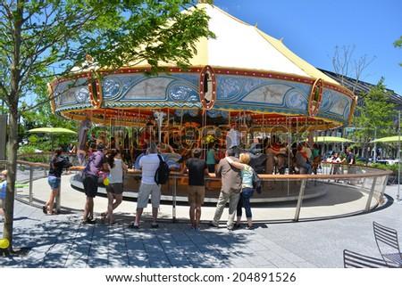 Boston Massachusetts, USA - July 5, 2014: Crowds enjoying the Carousel on the Rose Kennedy Greenway in downtown Boston.  - stock photo