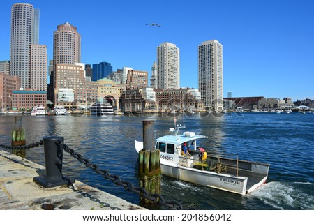 Boston Massachusetts, USA - July 5, 2014: Fisherman pulling into the harbor with their daily catch and the downtown skyline in the background in Boston.  - stock photo