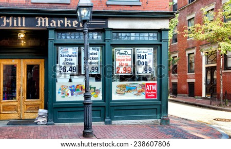 BOSTON-MAY 30, 2010: Old fashioned corner grocery store in the historic Beacon Hill neighborhood, where buildings and sidewalks are still constructed of red brick and a gas street lamp flickers. - stock photo