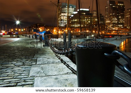 Boston's Rowe's wharf showing the granite walkways and the harbor chains with boats tied to the dock - stock photo