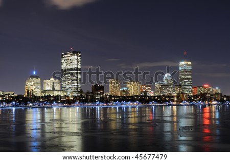 Boston skyline at night reflected on the frozen waters of Charles River - stock photo