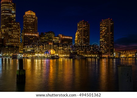 Boston skyline during the height of the blue hour with the lights of the city reflected in the harbor.