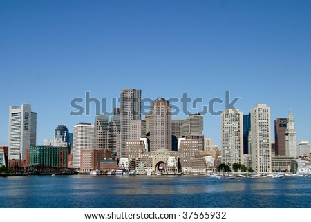Boston skyline from water with a blue sky