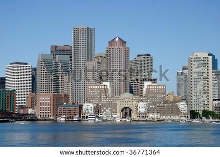 Boston skyline from water with a blue sky and water