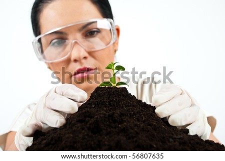 Botanical scientist checking ground in laboratory and looking to a small plant - stock photo
