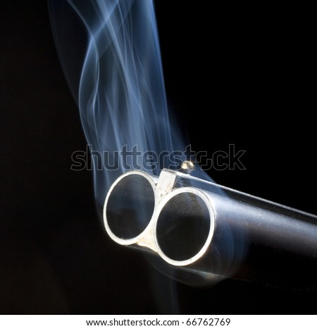 Both barrels of a double barreled shotgun belching smoke after shooting - stock photo