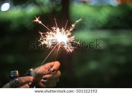 Both of little fireworks or firecracker sparking in holding hand