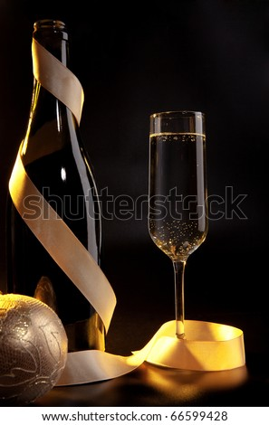 Bottle and champagne glass on a table - stock photo