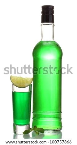 bottle and glass of absinthe with lime isolated on white