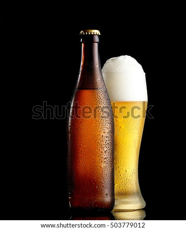Bottle and glass of beer on the wooden table over black background
