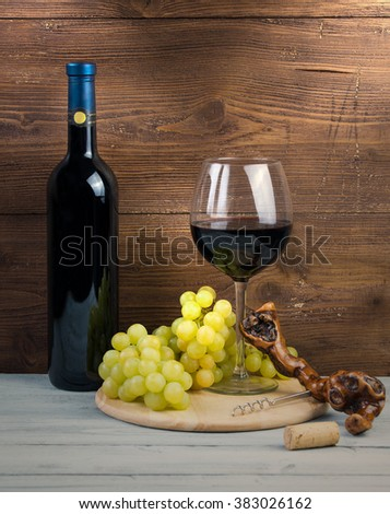 Bottle and glass of red wine, grapes and corkscrew made of vine