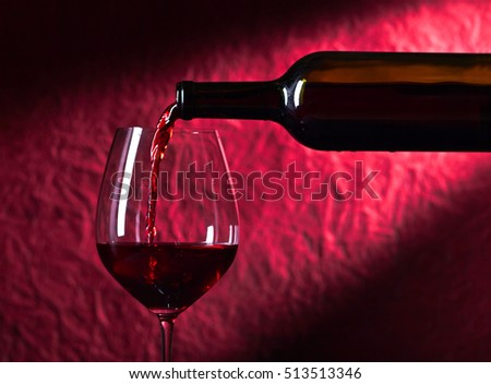 Bottle and glass of red wine on a dark red background