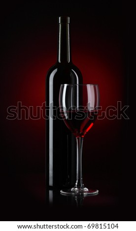 Bottle and glass of red wine on black background - stock photo