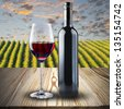Bottle and glass of red wine on natural wood pattern table with vineyard scene background - stock photo