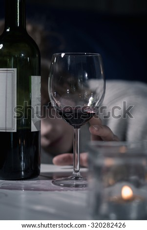 Bottle and glass of red wine on table