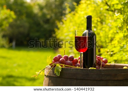 Bottle and glass of red wine with grapes on top of wooden barrel in vineyard - stock photo