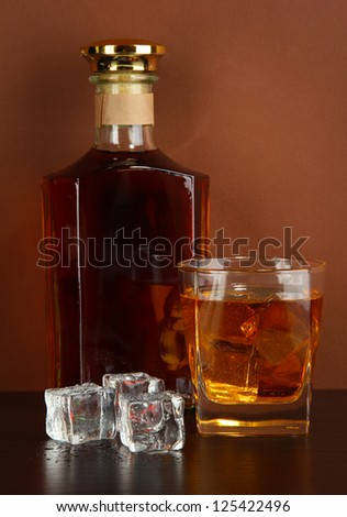 Bottle and Glass of whiskey and ice on brown background - stock photo