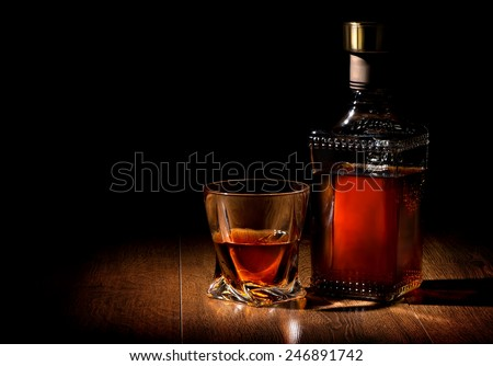 Bottle and glass of whiskey on a wooden table - stock photo