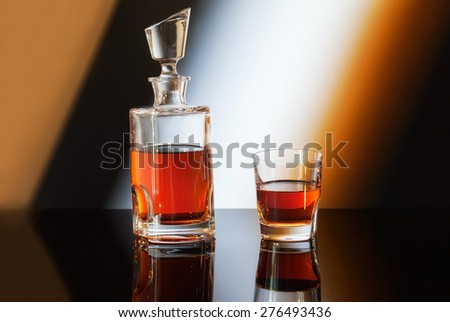 bottle and glass of whiskey on gradient background - stock photo