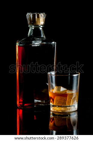 bottle and glass of whiskey with ice on dark background