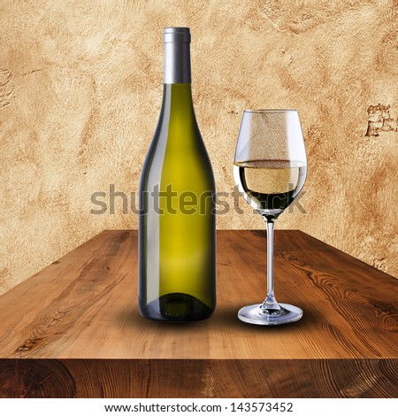Bottle and glass of white wine on wood table and grunge wall