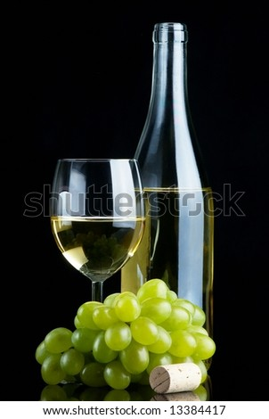 Bottle and glass of white wine with grapes and cork on black background - stock photo