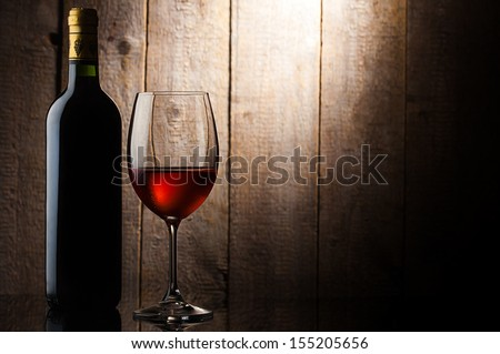 bottle and glass of wine in front of wooden background - stock photo