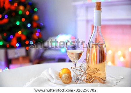 Bottle and glass of wine with Christmas decor against colorful bokeh lights background  - stock photo