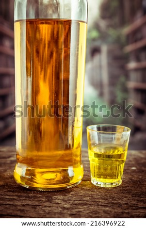 Bottle and glass shot with yellow liqour resembling whiskey, rum, tequila, spirit on wooden table - stock photo