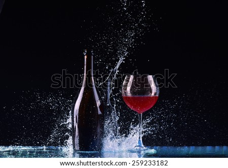 bottle and glass with red wine, water splash, wine on table on dark black background, big splash around Glass and bottle of red wine splash on black - stock photo
