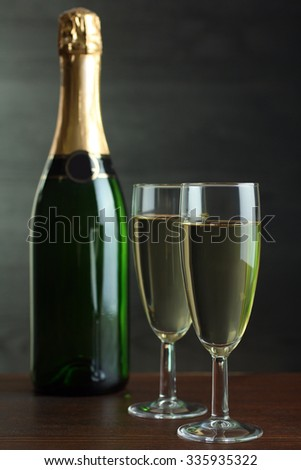 bottle and glasses of champagne on a wooden table on grey background - stock photo