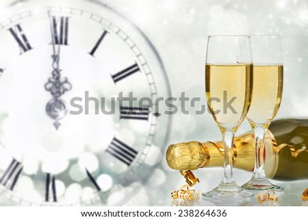 Bottle and glasses with champagne against holiday lights and clock close to midnight