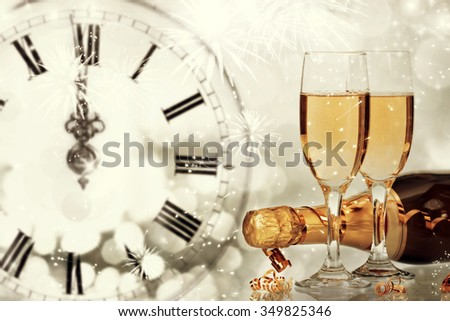 Bottle and glasses with champagne against holiday lights and clock close to midnight - stock photo
