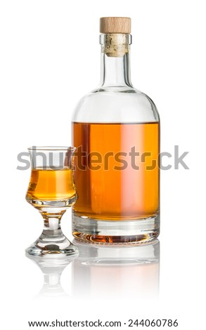 Bottle and schnapps glass filled with amber liquid - stock photo