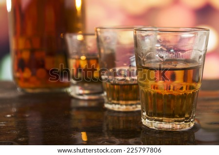 bottle and three shots of rum whiskey alcohol on wooden table over defocused lights background - stock photo