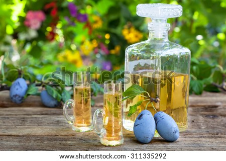 Bottle and two glasses with plum brandy - stock photo