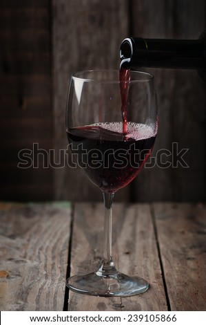 Bottle and wine glass in wooden back ground - stock photo