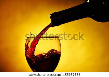Bottle and wine glass in yellow back ground - stock photo