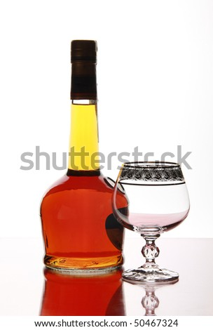 Bottle beautiful elite cognac and empty goblet on mirror table - stock photo