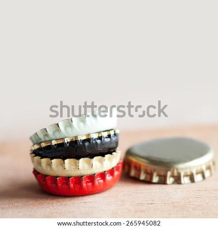 Bottle caps on wooden background. Pastel colors. Macro view (soft focus) - stock photo