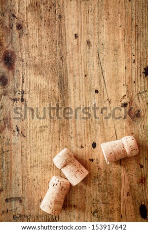 Bottle corks for champagne or wine on a wooden background with copyspace for your festive or New Year greeting