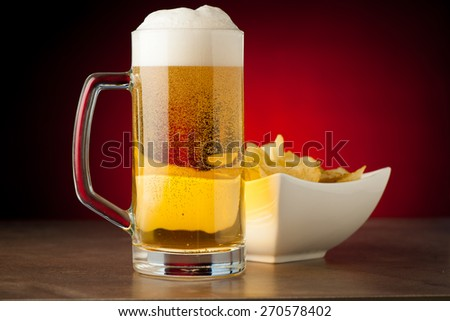 bottle, glass of beer and potatoe chips on stone table over red background - stock photo