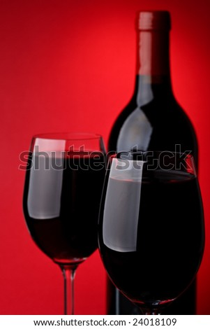 Bottle of a red vintage wine and two glasses on a red background