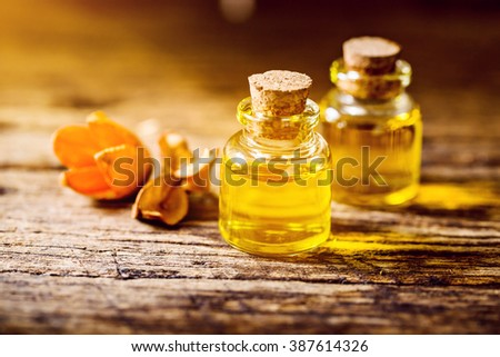 bottle of aroma essential oil with dry flower on wooden table, spa concept. - stock photo