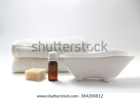Bottle of aroma oils, soap, a bathtub figurine, and towel on white back ground. - stock photo