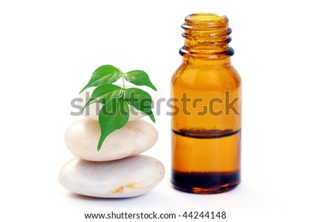 bottle of aromatherapy oil and fresh green leaves - beauty treatment - stock photo