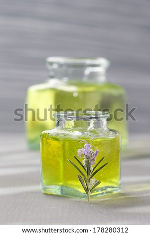 bottle of aromatherapy oil and fresh green leaves - relaxing and beauty treatment-  - stock photo