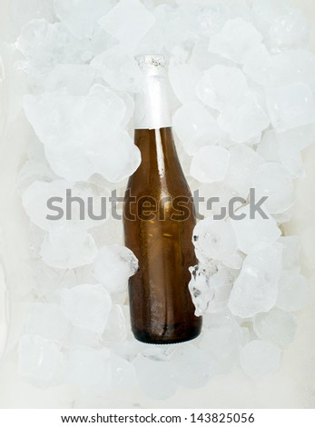 Bottle of beer and ice cubes - stock photo