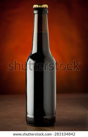 Bottle of beer on a stone table over brown background
