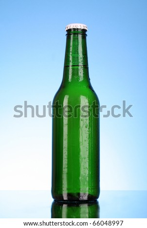 Bottle of beer on blue background - stock photo
